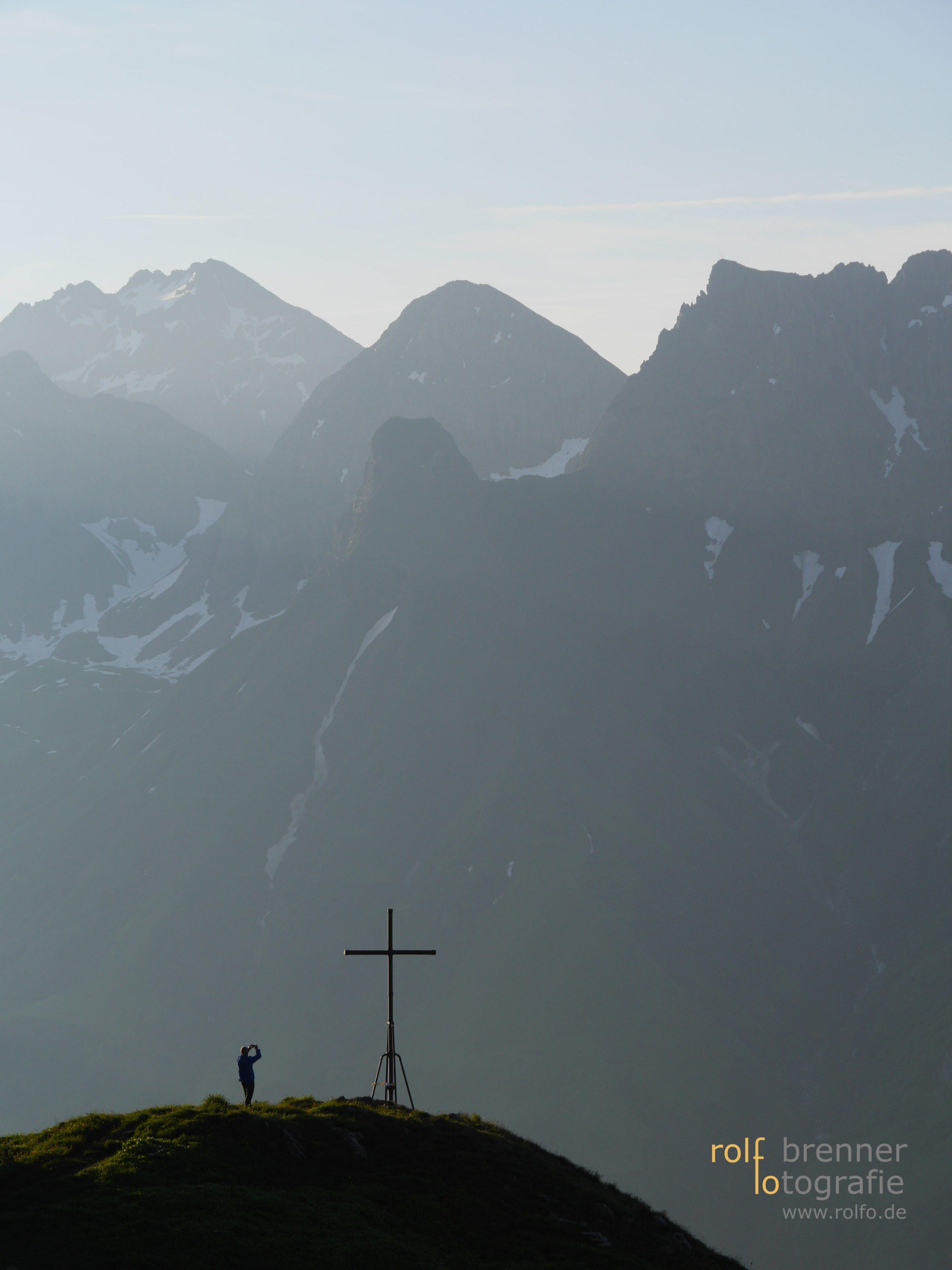 Mann fotografiert Gipfelkreuz bei der Mindelheimer Huette